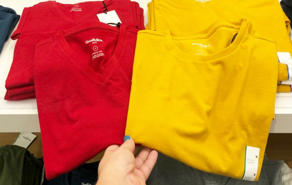 person holding up solid colored red and yellow men's basic tees