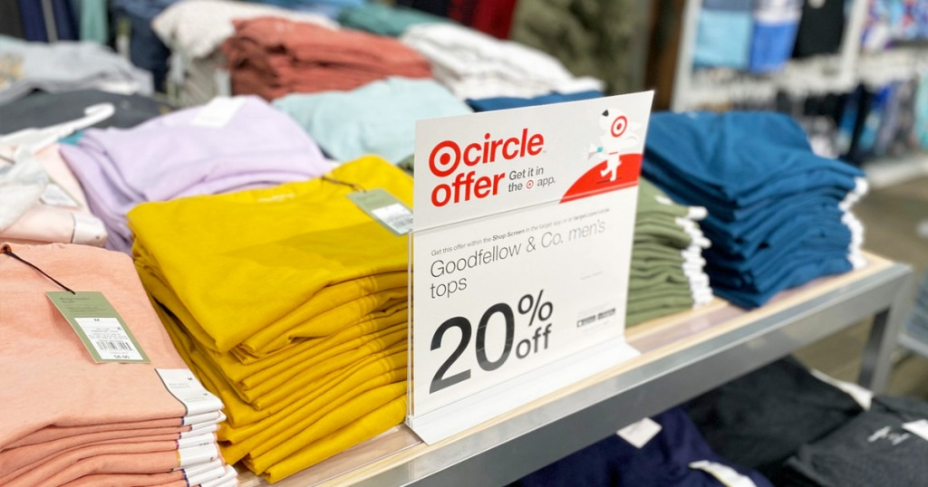 store display table full of folded men's basic tees with 20% off sale sign