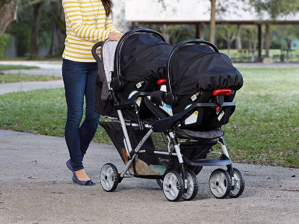 woman pushing double stroller outside