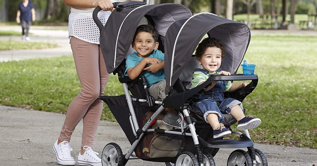 woman pushing two children in double stroller outside