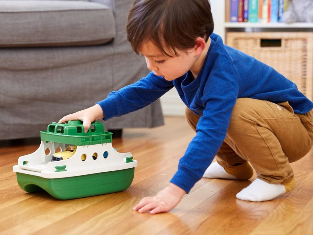 little boy squatting on the floor playing with a plastic green toy ferry boat