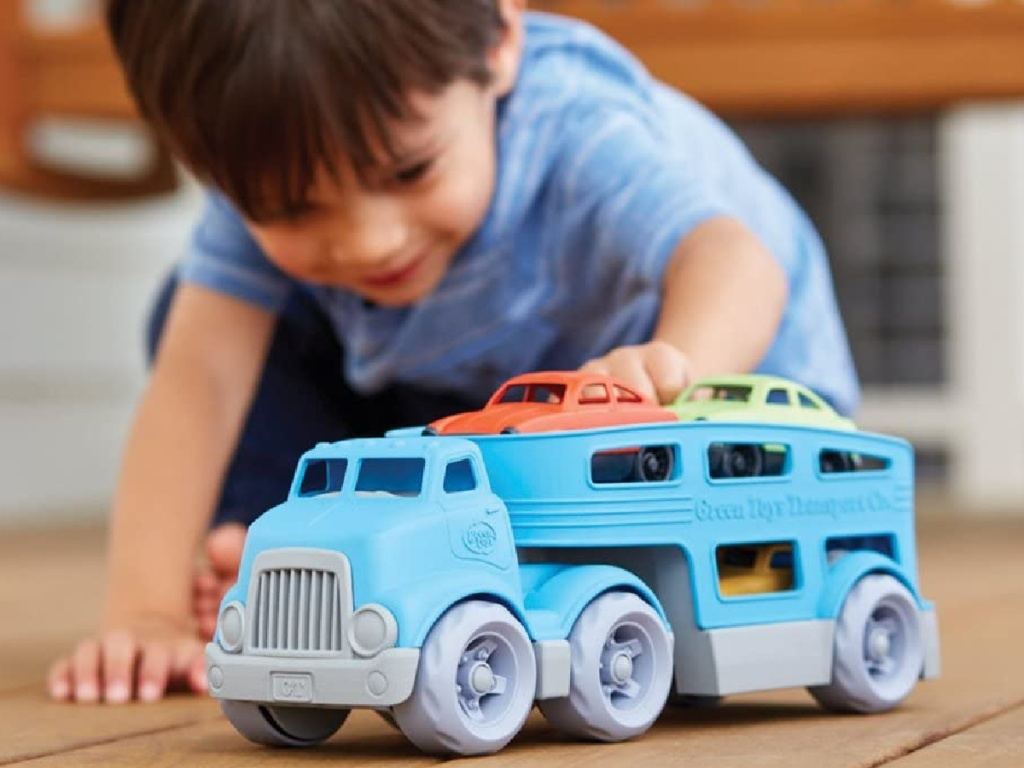 little boy kneeling on the floor playing with a green toys blue plastic truck