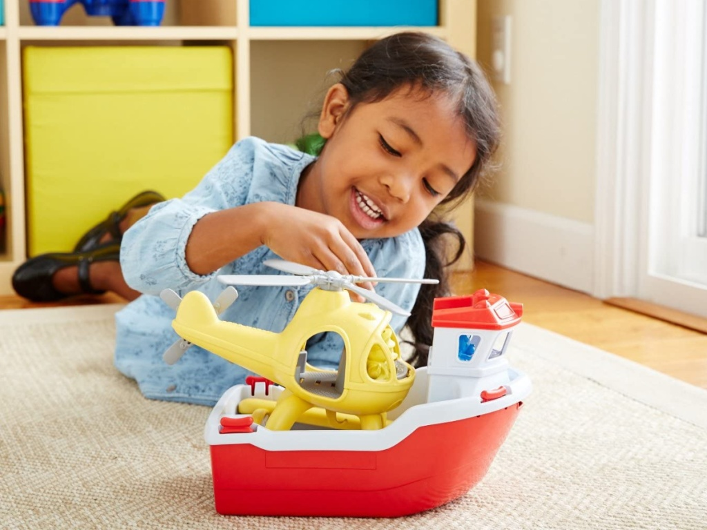 little girl laying on the floor playing with a green toys plastic boat and helicopter