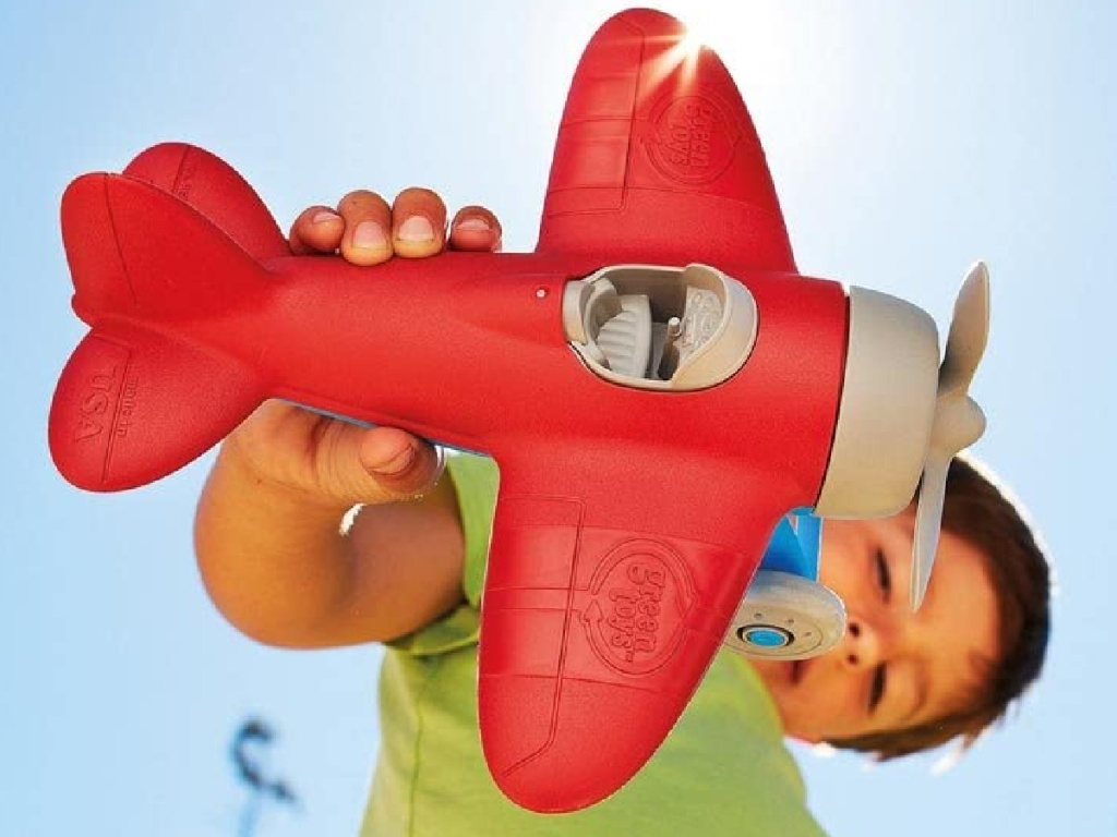 little boy holding a red green toys plastic airplane