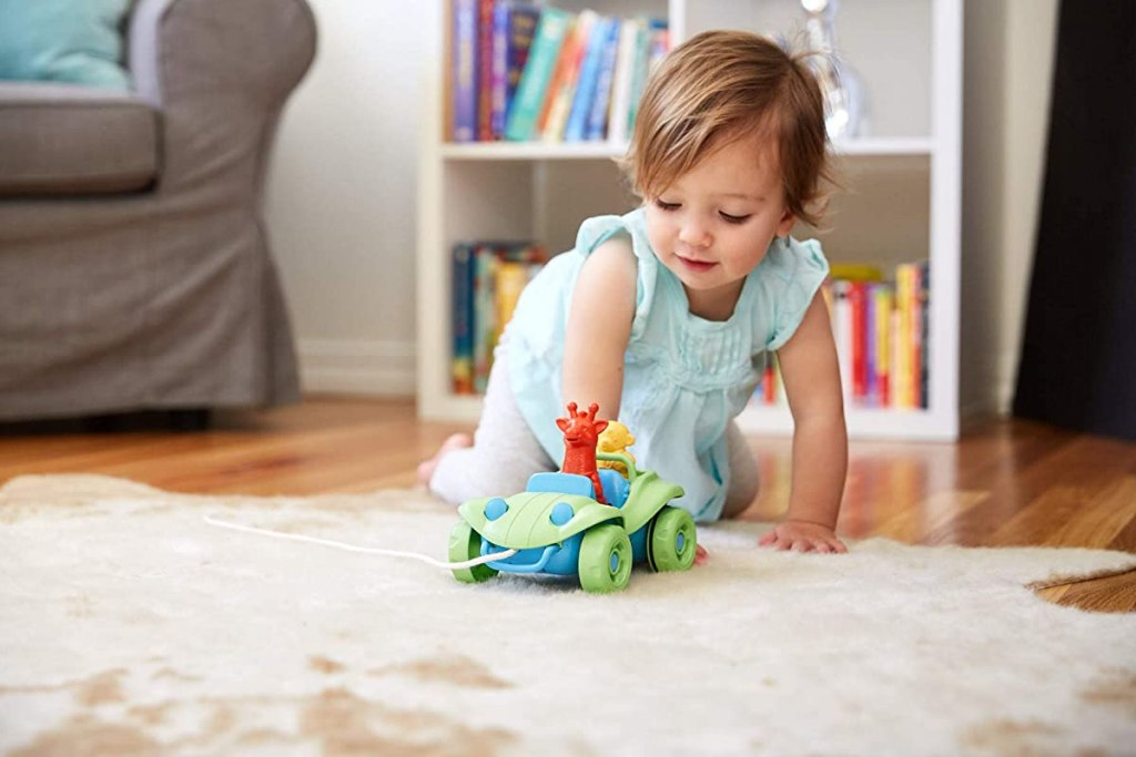 baby playing with a toy buggy