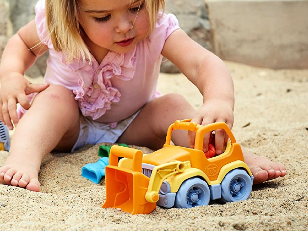 little girl playing with a Green Toys Scooper Construction Truck