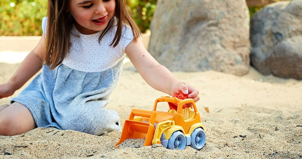 little girl on beach playing with a Green Toys Scooper Construction Truck