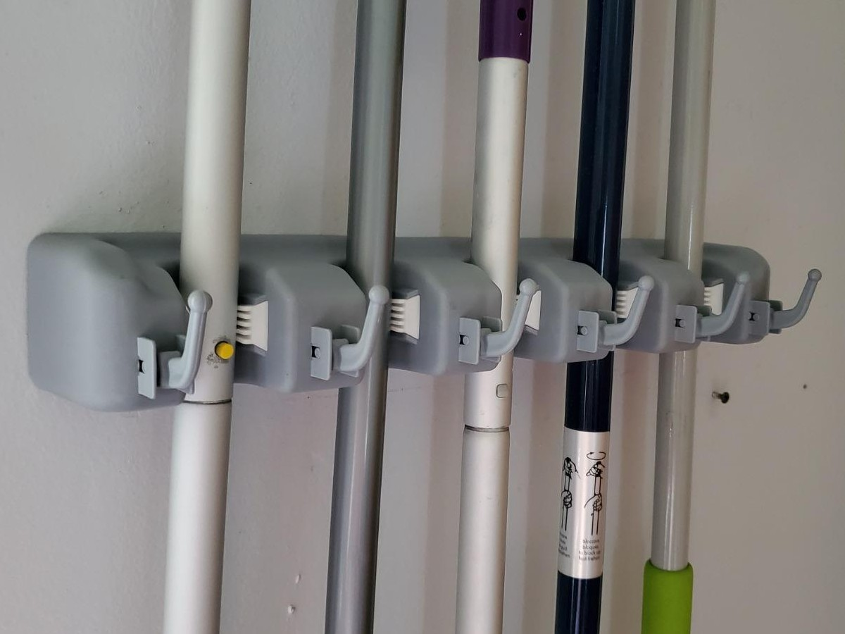 gray wall-mounted mop and broom holder