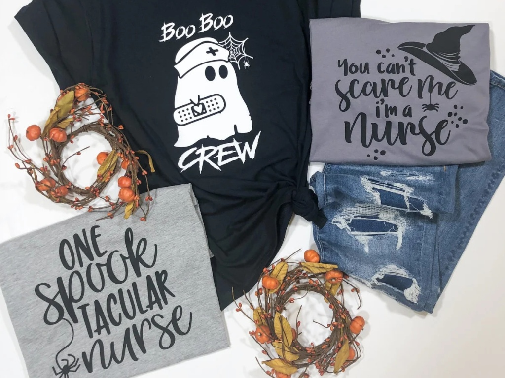 gray graphic Halloween themed tees, black graphic Halloween tee, jeans, and pumpkin wreaths