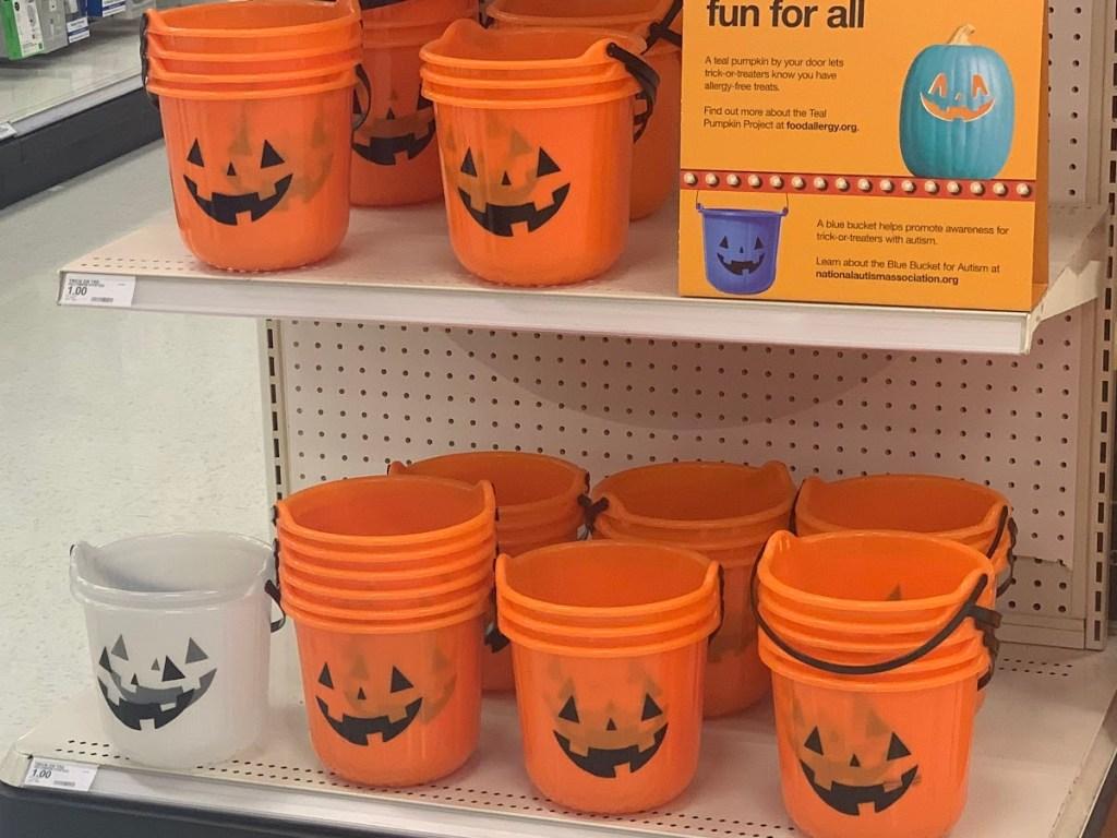 orange and clear Halloween pumpkin buckets on store shelf