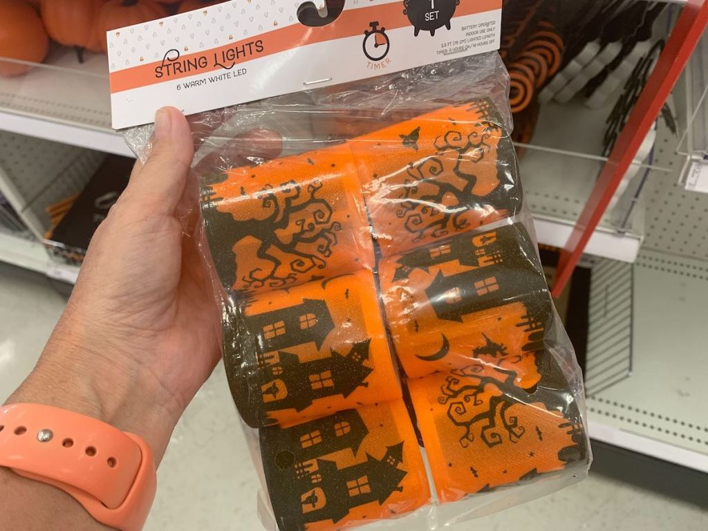 woman's hand holding up a set of Halloween String Lights in packaging