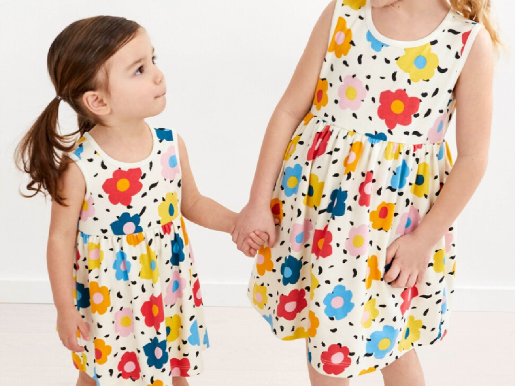 2 little girls wearing bright floral sleeveless dresses