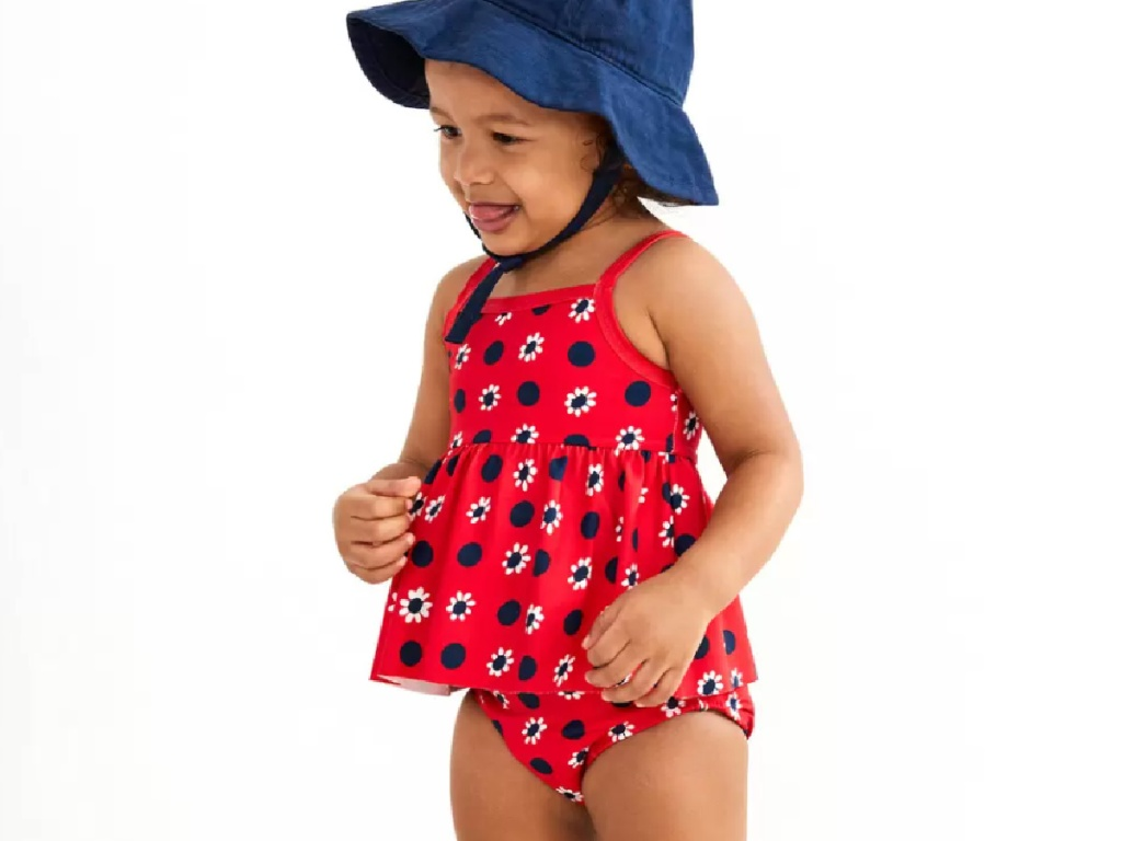 toddler girl wearing a 2-piece red swimsuit and blue bucket hat
