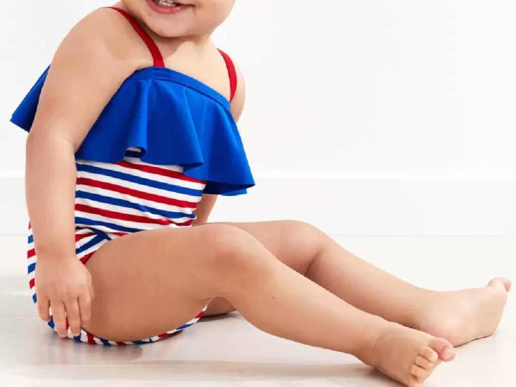 infant baby girl sitting sideways wearing a red, white and blue striped swimsuit
