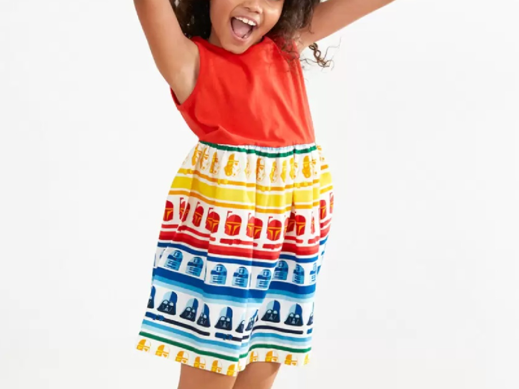 little girl jumping in the air wearing a bright rainbow colored sleeveless star wars dress