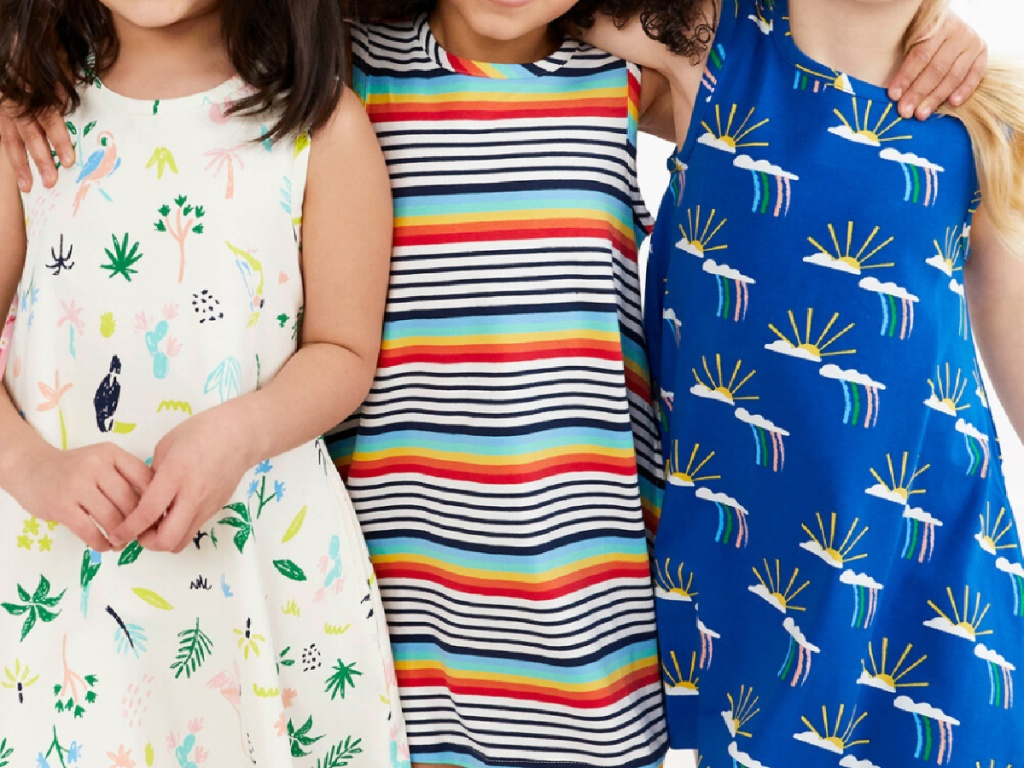 3 little girls standing next to each other wearing colorful sleeveless dresses