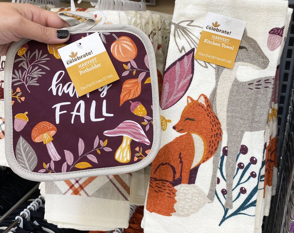 person holding up a matching pot holder and kitchen towel that say happy fall with fall leaves and animals print