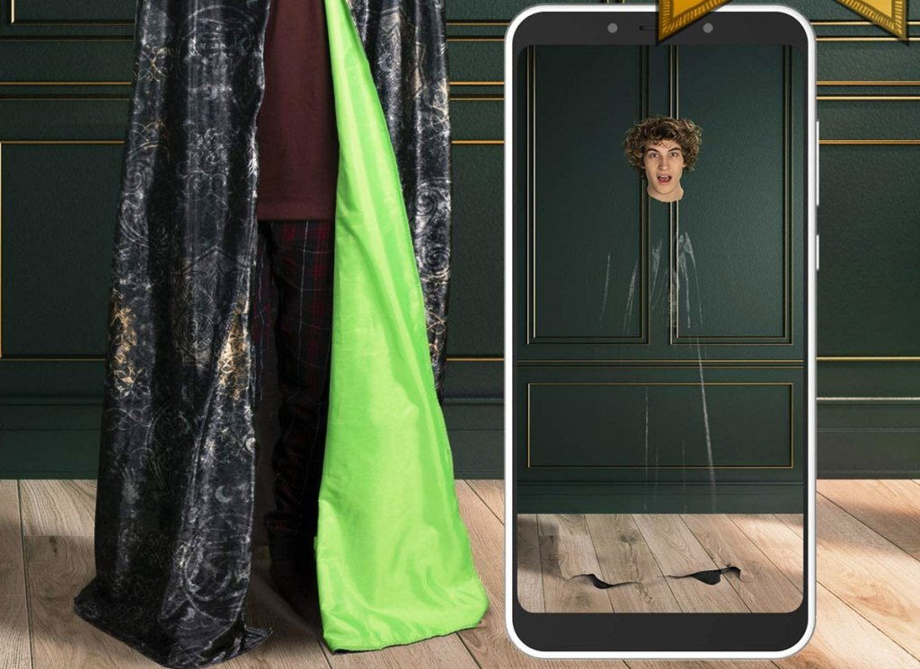 man wearing Harry Potter cloak and smartphone showing picture of him as only a floating head