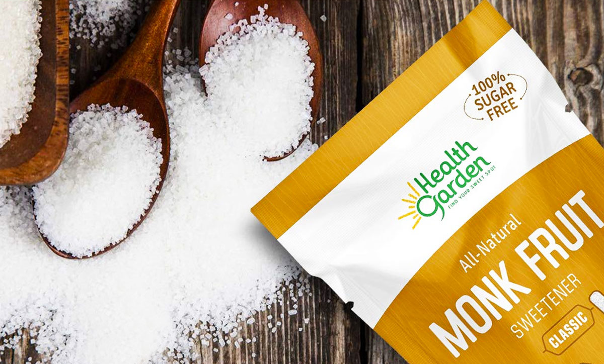 brown and white bag of monk fruit sweetener on wood table next to wooden spoons and spilled sweetener