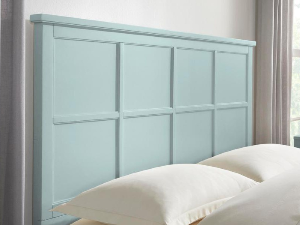 light blue grid style headboard attached to a bed with cream colored pillows