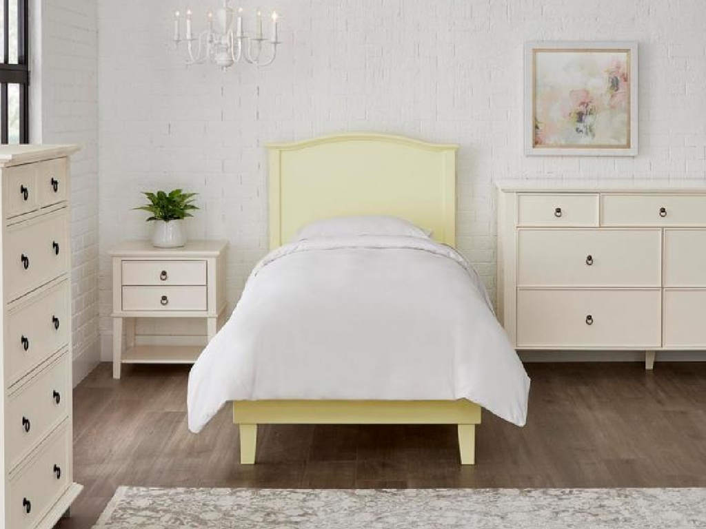 yellow twin bedding with a white blanket surrounded by white bedroom furniture