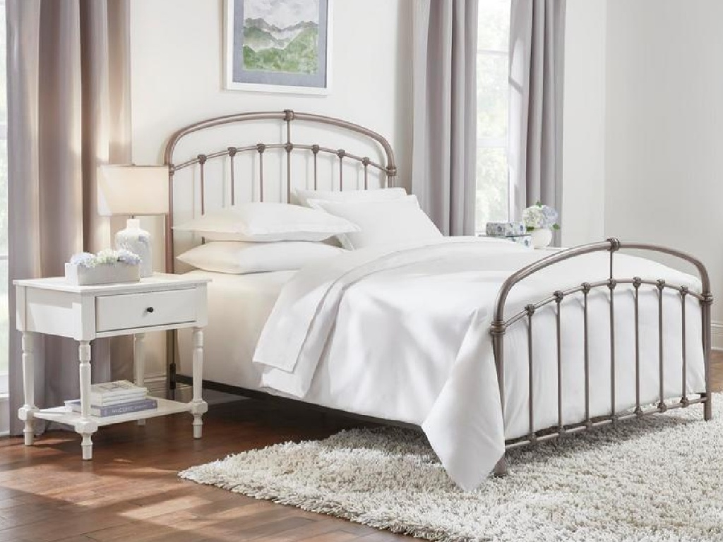 Pewter colored metal bed with white bedding surrounded by white bedroom furniture