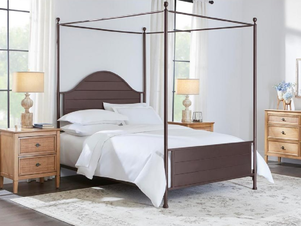 bronze colored metal canopy bed with white bedding in a bedroom with brown bedroom furniture