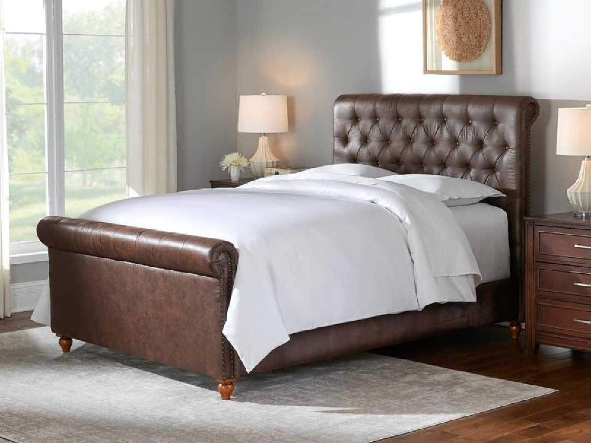 brown leather sleigh bed with white beddingn a bedroom nexto night stands and a lamp