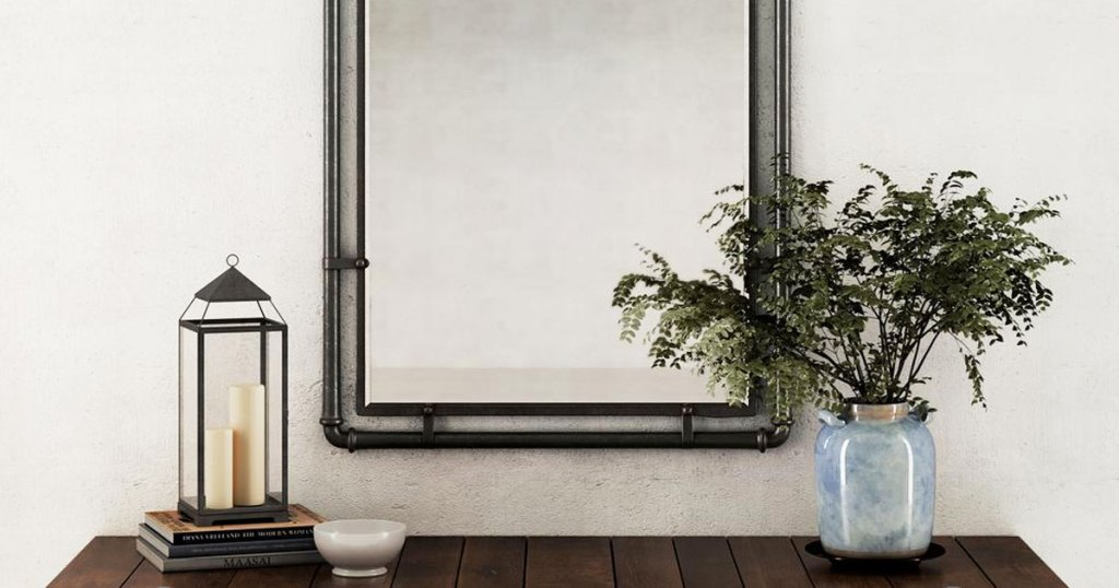 metal pipe framed wall mirror above accent table with plant and lantern