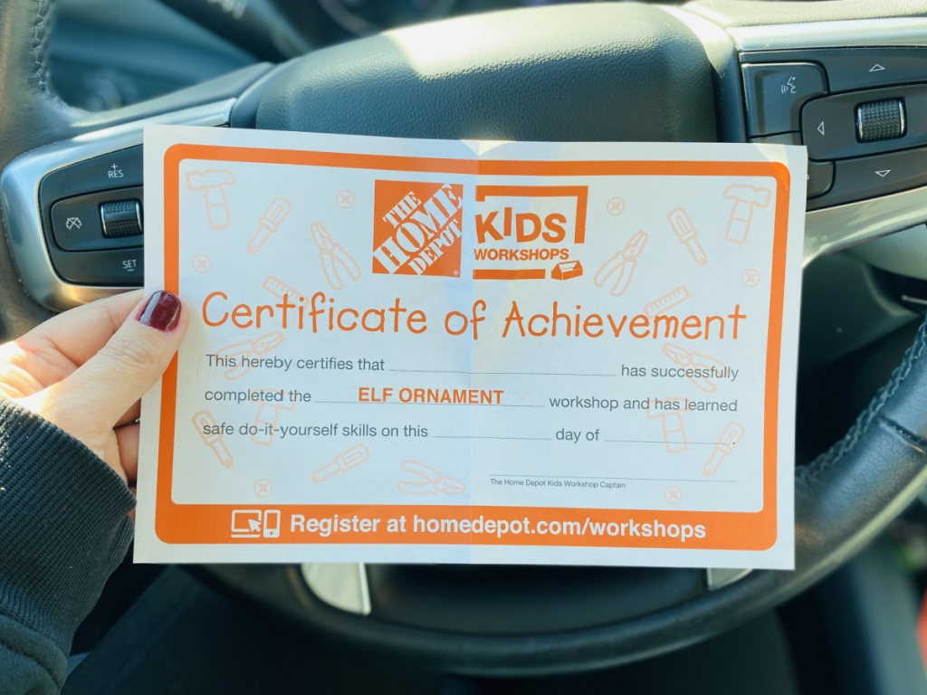 manicured hand holding a home depot kits activities kit certificate of achievment