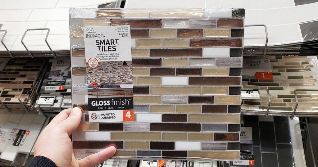 person holding up a set of peel and stick tile backsplash at Home Depot
