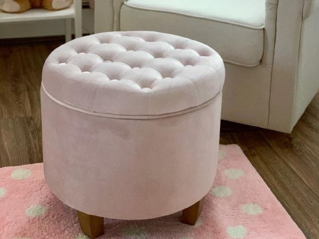 blush pink rounded tufted ottoman sitting on pink and white polka dot capet