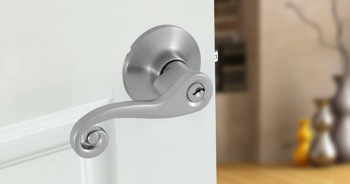 close up of Honeywell Scroll Satin Nickel Locking Door Lever Set on white door