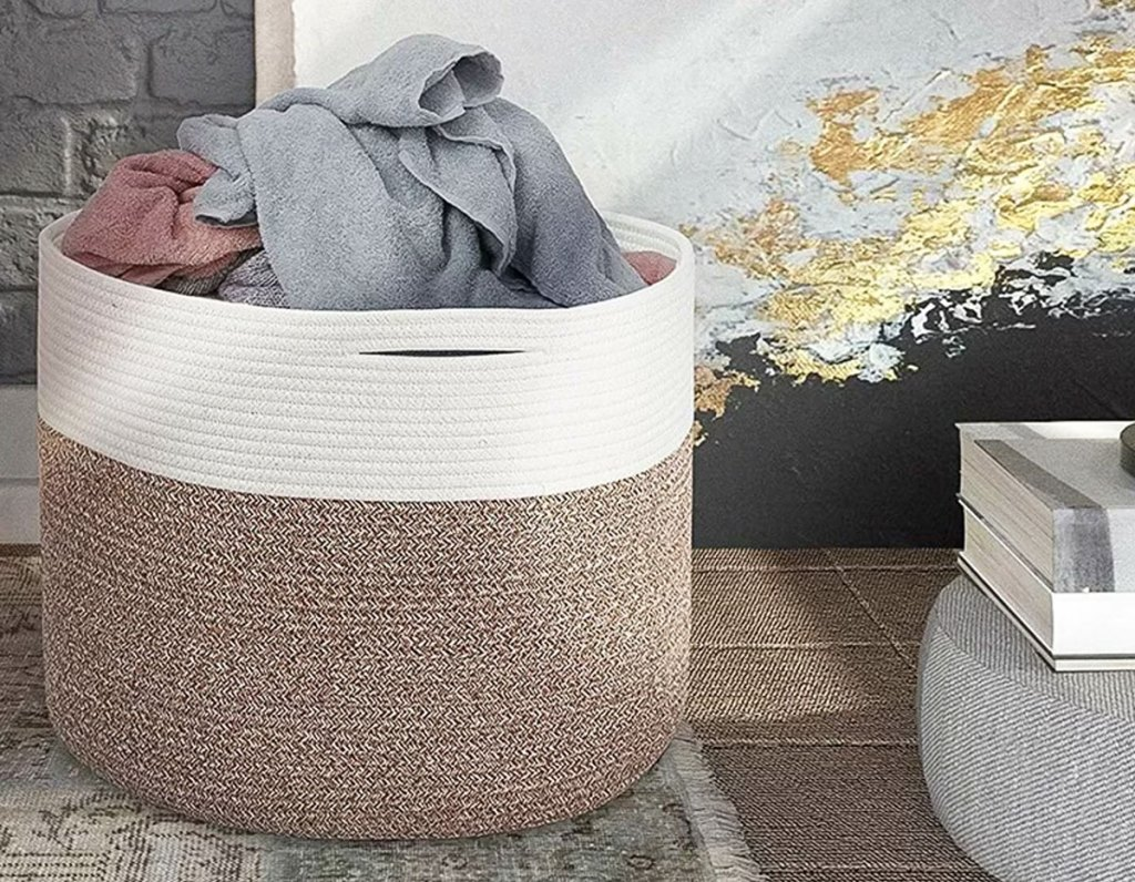 brown and white fabric basket on floor with clothes inside