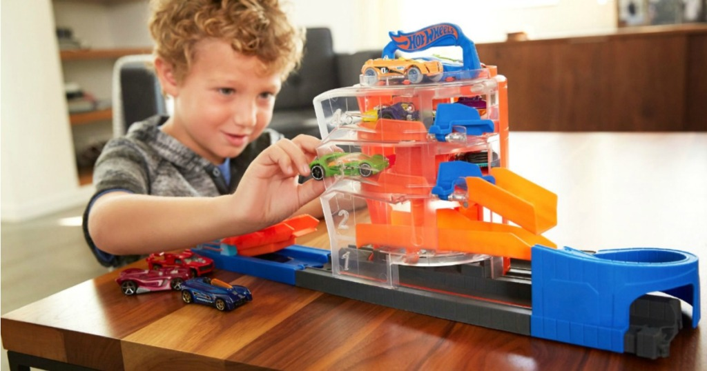 young boy playing with hot wheels track