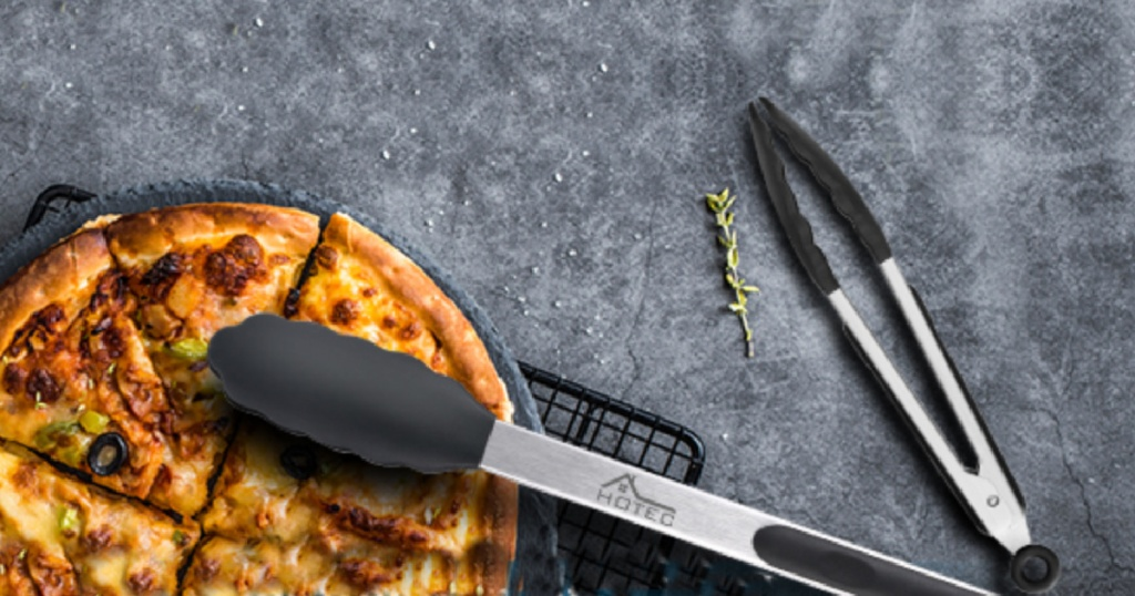 set of two metal tongs with silicone tips sitting next to a pizza