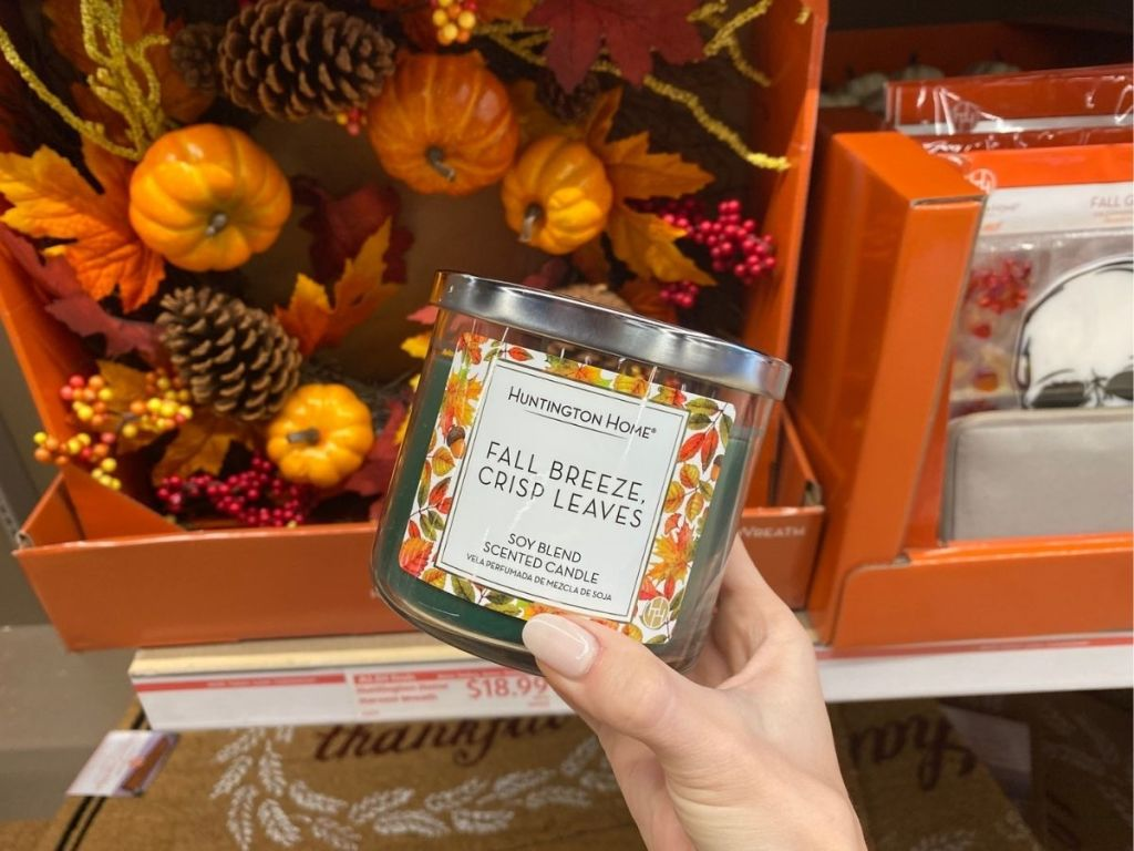 hand holding Huntington Home Fall Breeze Crisp Leaves Candle in store