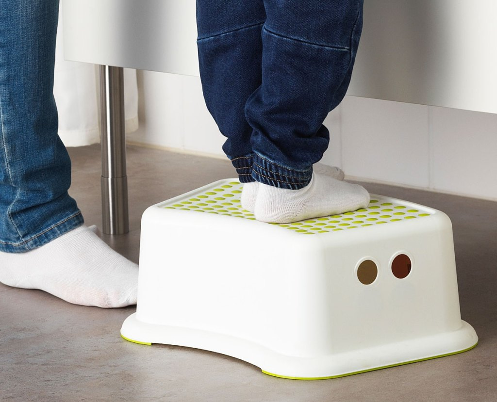 toddler in socks and jeans standing on a white and green kids stool