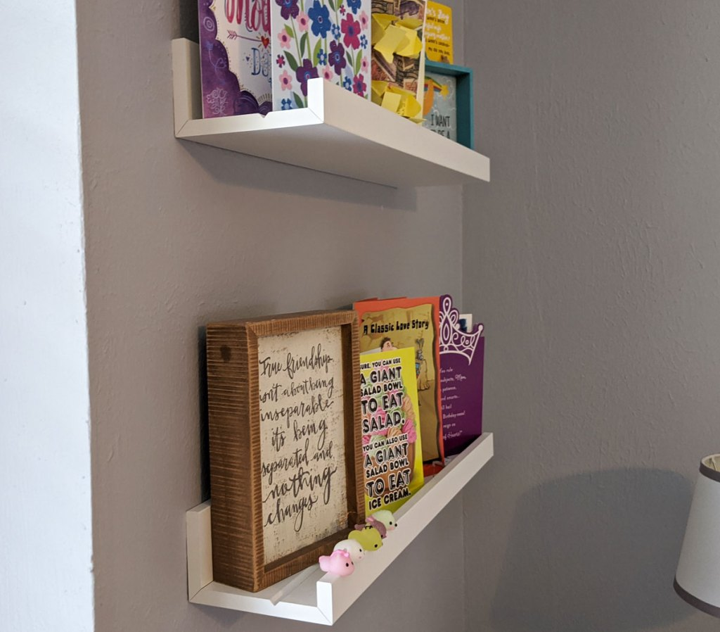 two white picture shelves on grey wall filled with decor and greeting cards