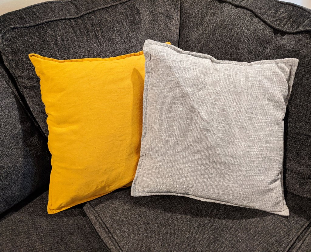 light grey and golden yellow throw pillows on a dark grey couch