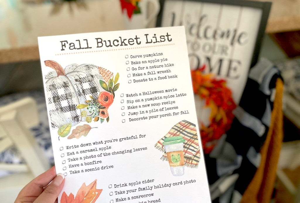 hand holding a fall bucket list in front of home decor