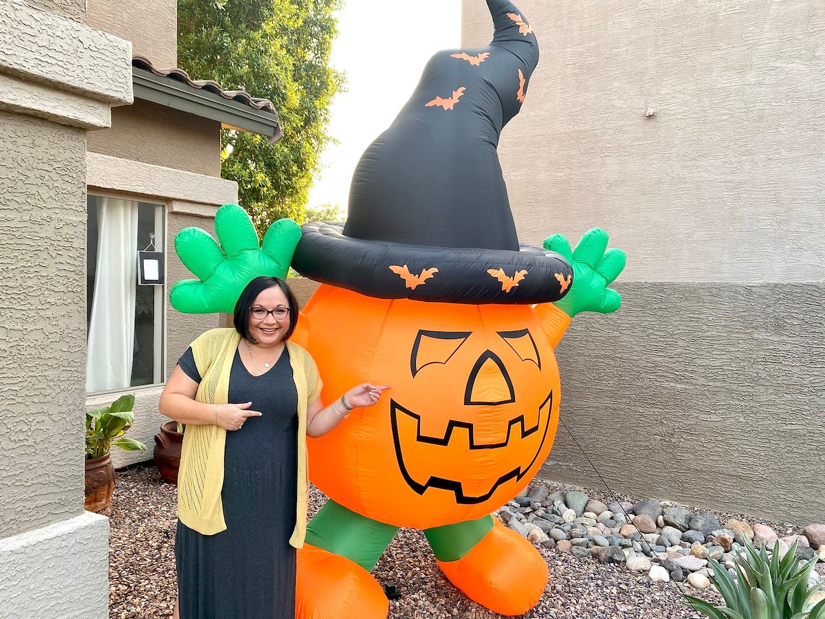 woman standing next to giant inflatable pumpkin with black hat