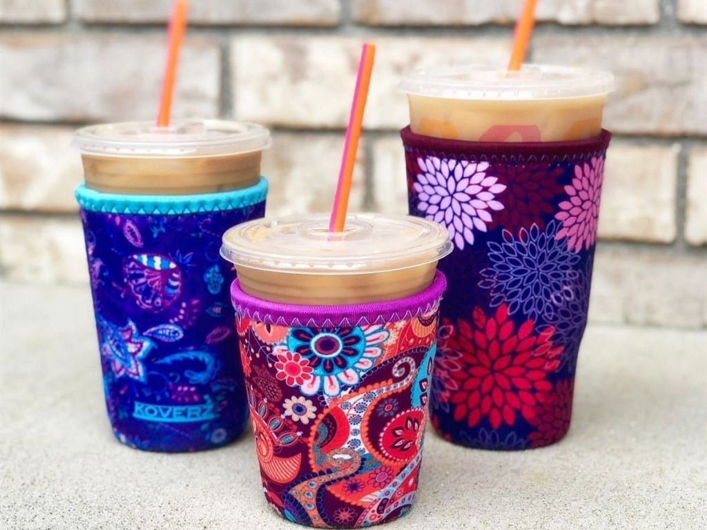 patterned covers around iced coffee cups with brick wall in background