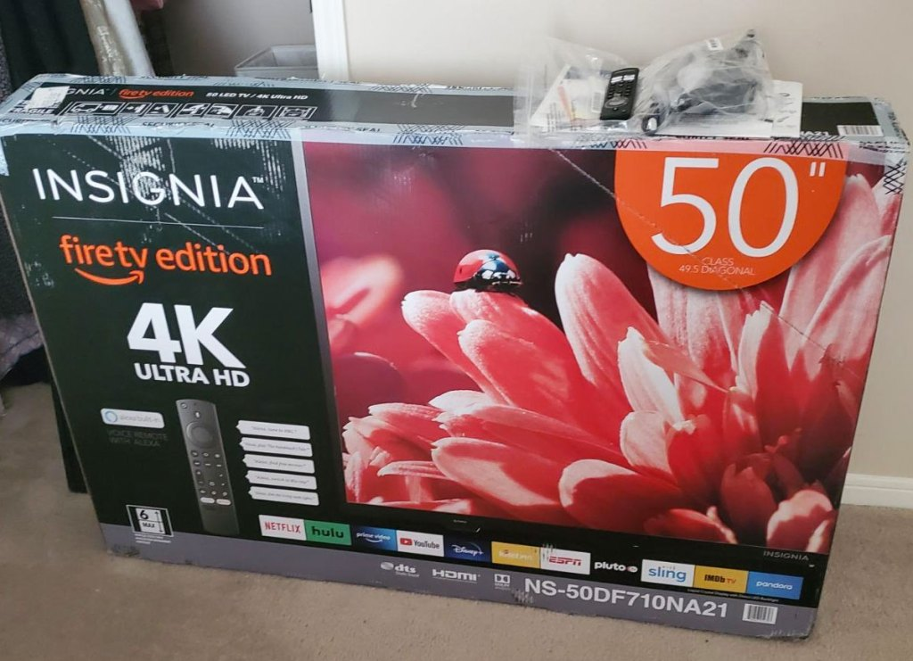 """box for an insignia 50"""" smart tv sitting on brown carpet in room"""