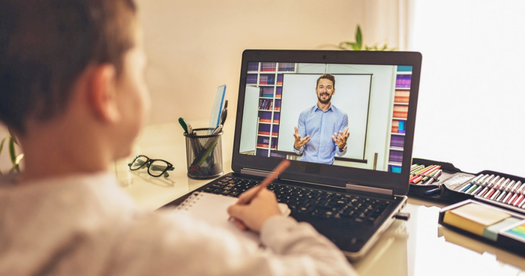 boy sitting at computer with a man on screen teaching an online course