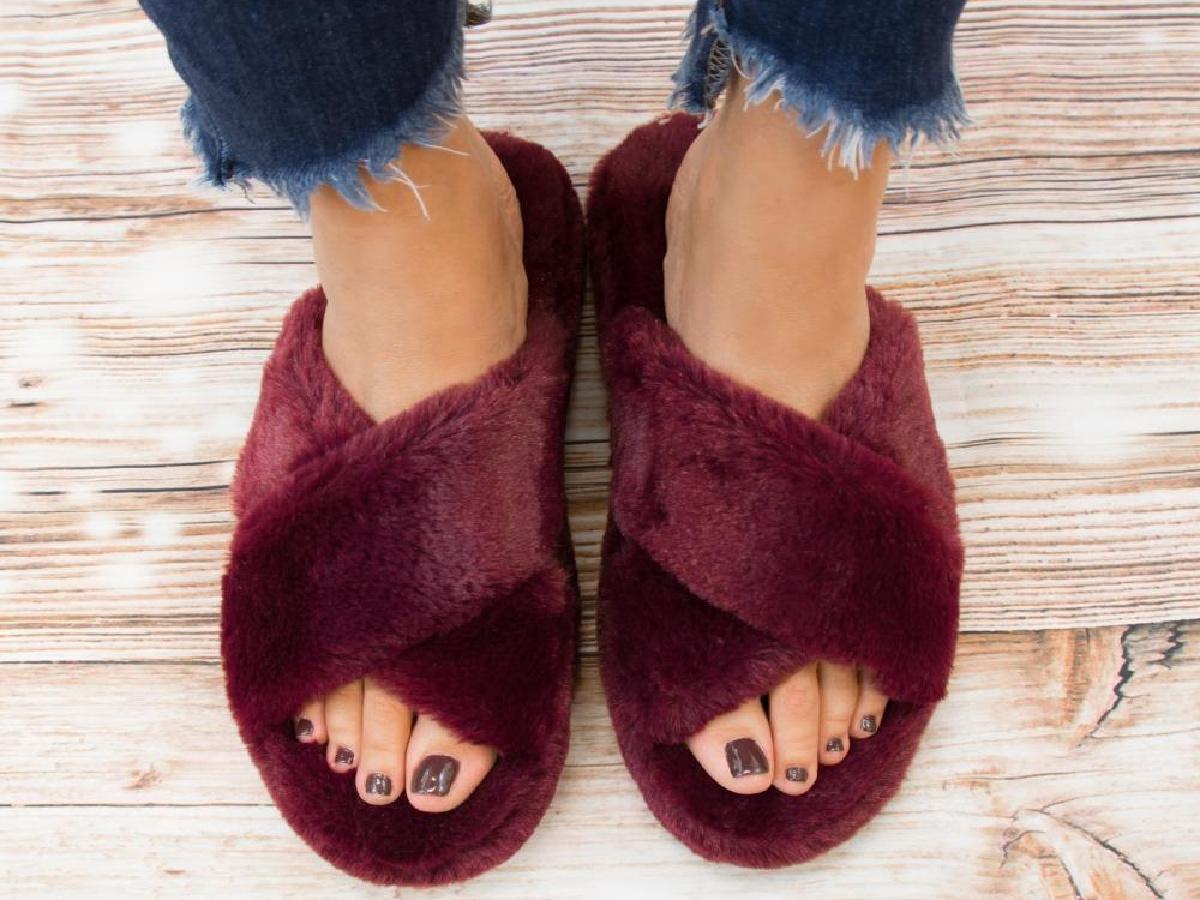 legs wearing burgundy open-toed slippers
