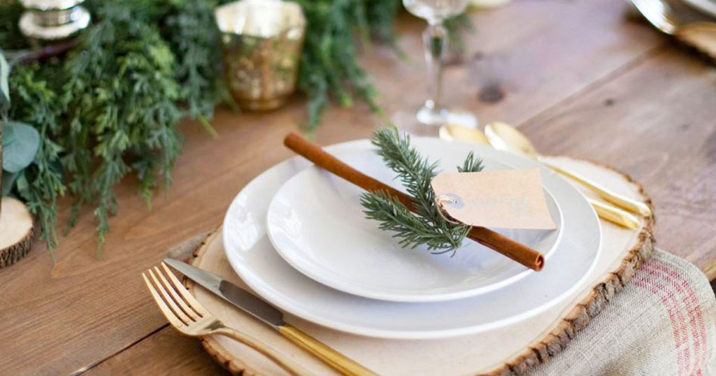 round white dinnerware set on table with sprigs of rosemary on top