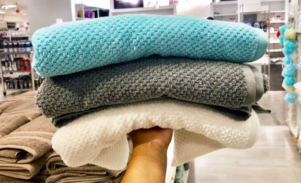 person holding up a stack of white, grey, and blue colored textured bath towels