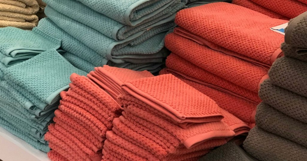 folded stacks of textured bath towels and matching hand towels on store display table
