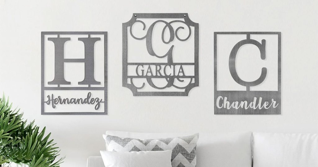 three rectangular steel monogrammed family name plaques on wall above white couch